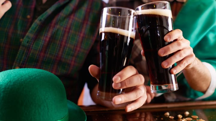 Two people drinking beer on St. Patrick's Day.