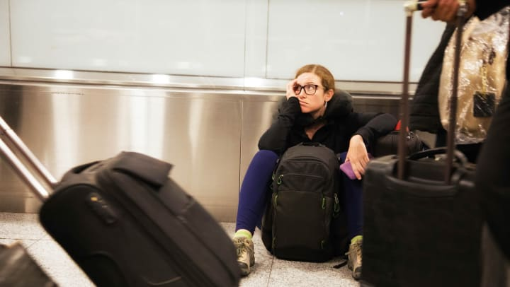 Woman sitting on the floor of an airport as people go by