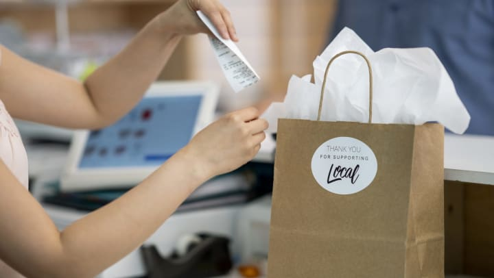 """Retail worker placing receipt in a paper shopping bag with a """"Thank You for Supporting Local"""" sticker on it."""