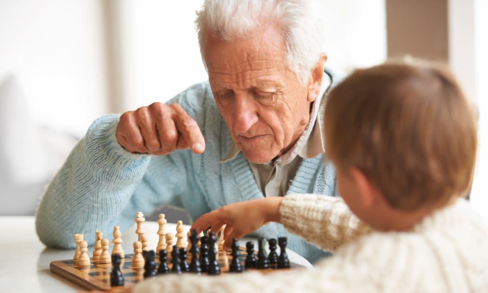 A resident and a child playing a game of chess at Amaran Senior Living in Albuquerque, New Mexico.