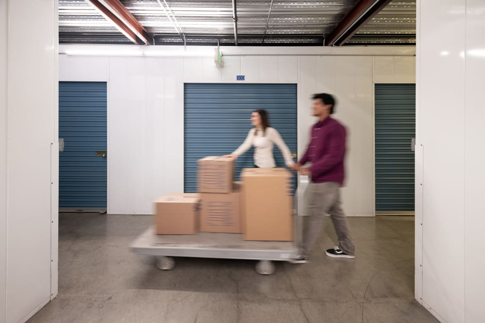 A young couple moving boxes into Hayward Storage LLC in Hayward, California