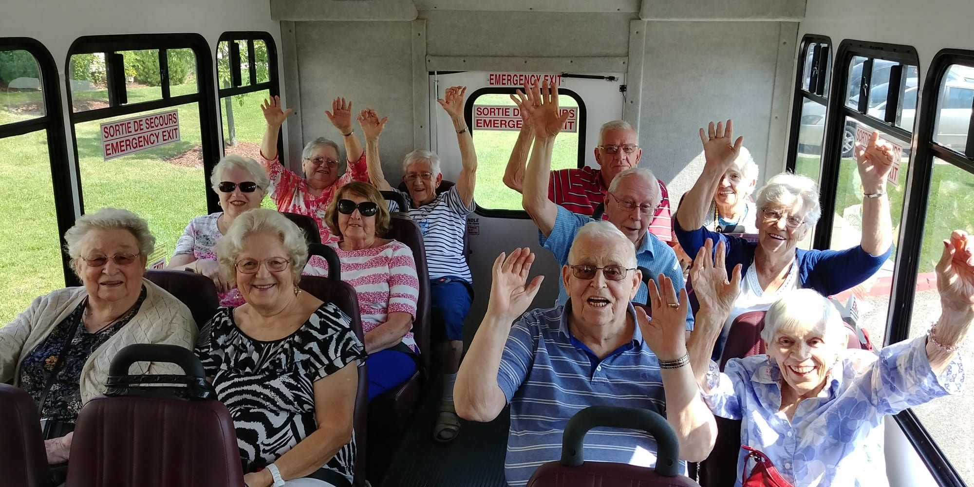 Residents with their hands in the air on the bus at Palms at Bonaventure Assisted Living in Ventura, California