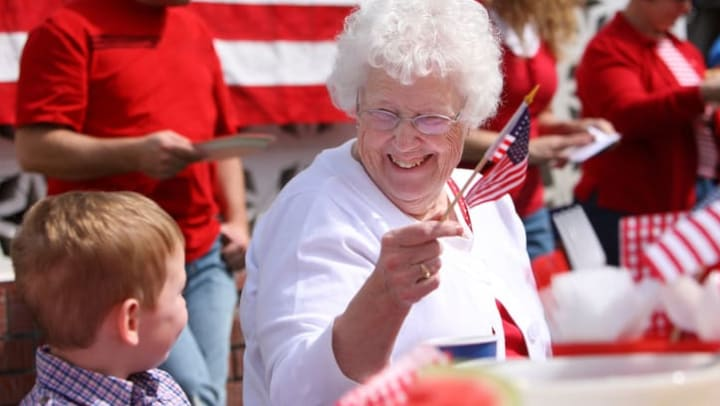 Elderly woman waves an American flag while smiling at a young boy near {{location_name}} in {{location_city}}, {[location_state_name}}