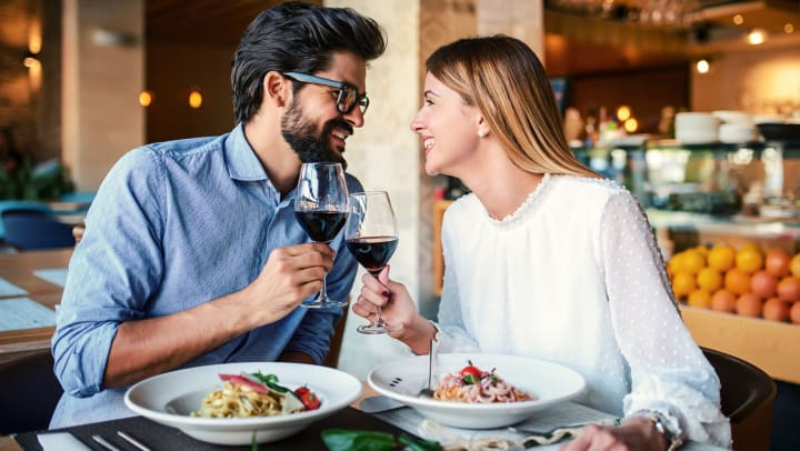 A man and a woman looking at each other and smiling while they clink wine glasses full of red liquid in front of pasta dishes.
