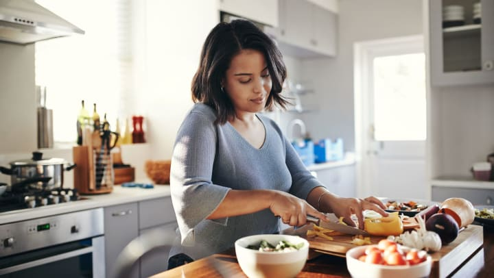Woman chopping ingredients in her kitchen.