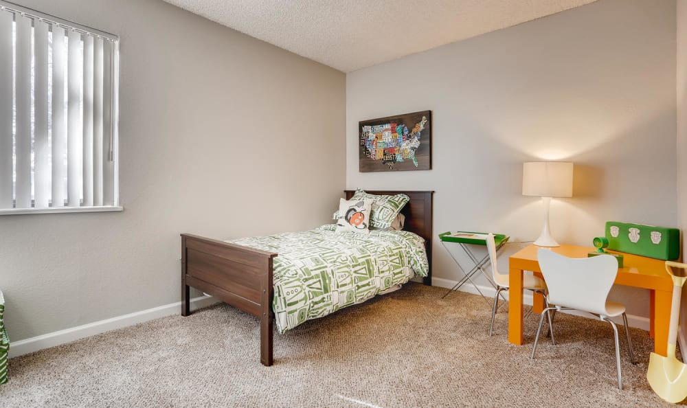 large bedroom with twin sized bed and orange desk with lamp at The Ranch at Bear Creek Apartments & Townhomes in Lakewood, Colorado