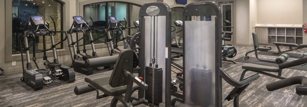 A fitness center with individual workout stations at Sommerall Station Apartments in Houston, Texas