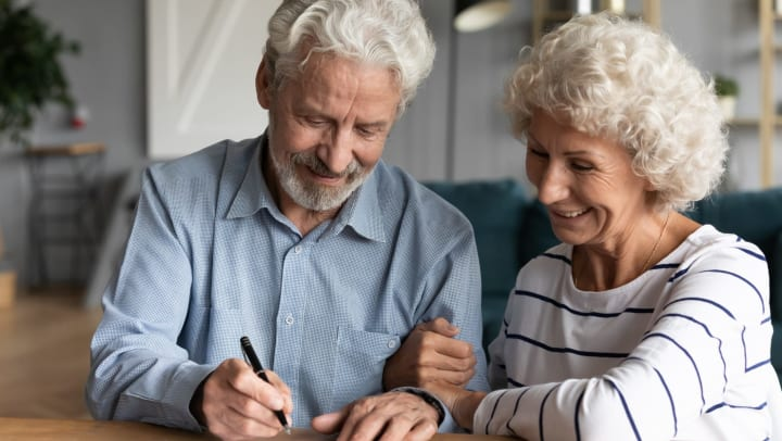 Senior man and woman sitting at a table, smiling, as man prepares to sign a paper.