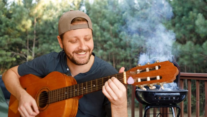 Man smiling and playing the guitar with a smoking BBQ in the background.