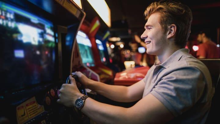 A man sitting at an arcade game in an arcade.