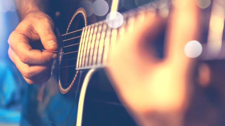 Close-up of person playing a guitar