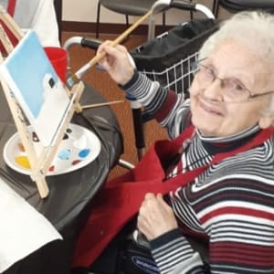 Resident Violet painting a picture at his Dare to Dream event at Milestone Senior Living in Woodruff, Wisconsin