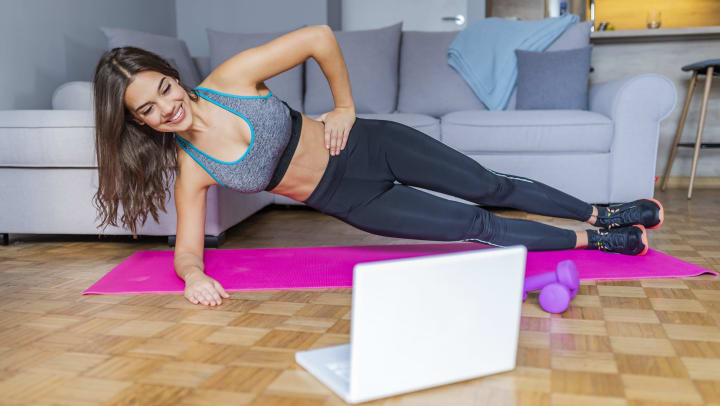 A woman in workout clothing holds a side plank position on a yoga mat on the floor of her living room, as she looks at her laptop.