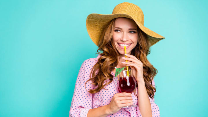 Woman in sun hat and polka dot dress again blue background, holding a cocktail glass, pinching the straw between her teeth and smiling.