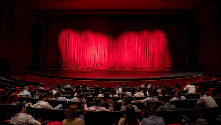 An audience waiting for the red stage curtains to open at a performance