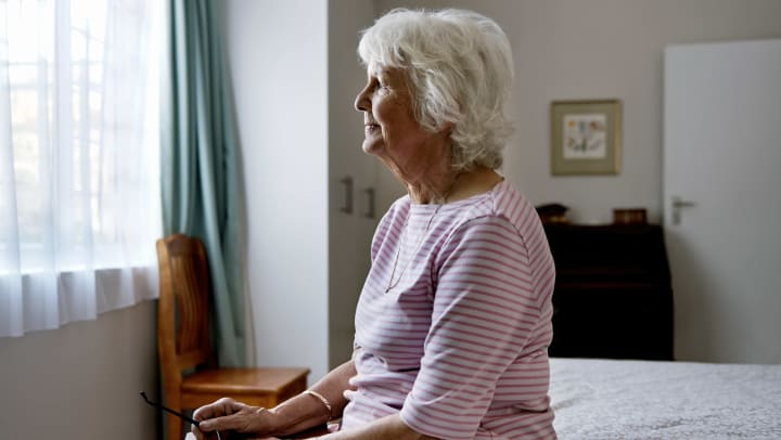 An elderly woman sits on her bed
