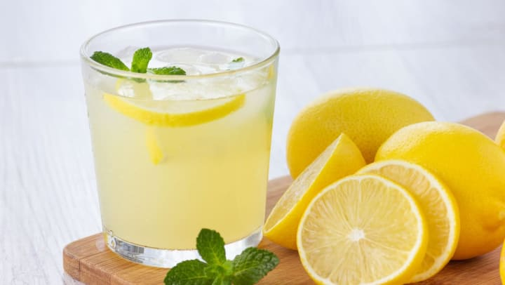 Fresh citrus lemonade drink with sliced lemon and mint on a wooden cutting board.
