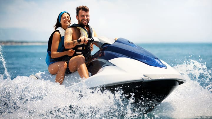 Man and woman riding on a jet ski, smiling.