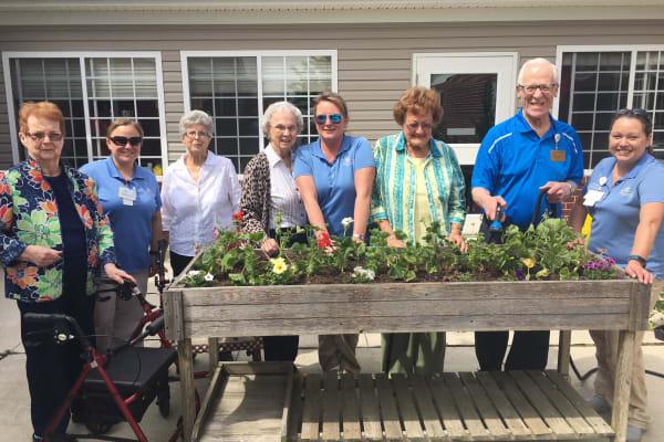 Residents around a flower garden at Cooper Trail Senior Living in Bardstown, Kentucky
