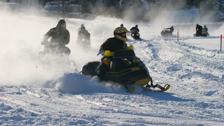 Racers on vintage snowmobiles race around a track