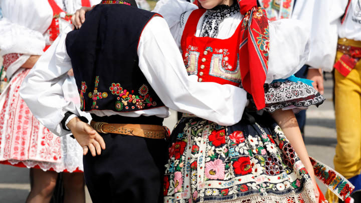 A couple dancing in colorful traditional Czech costumes, with more dancers visible in the background.