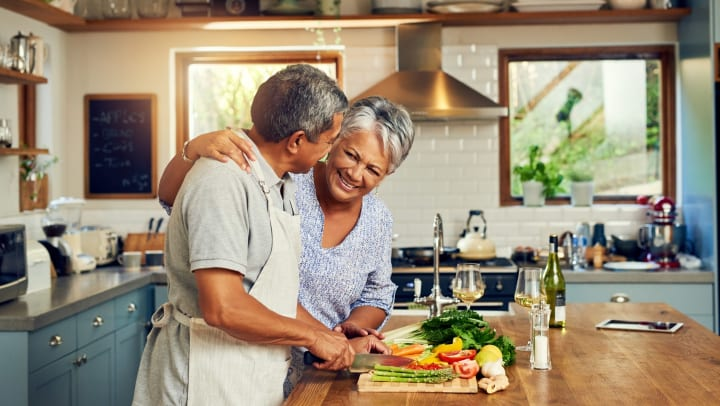 Mature man and woman in a kitchen smiling and cooking food together.