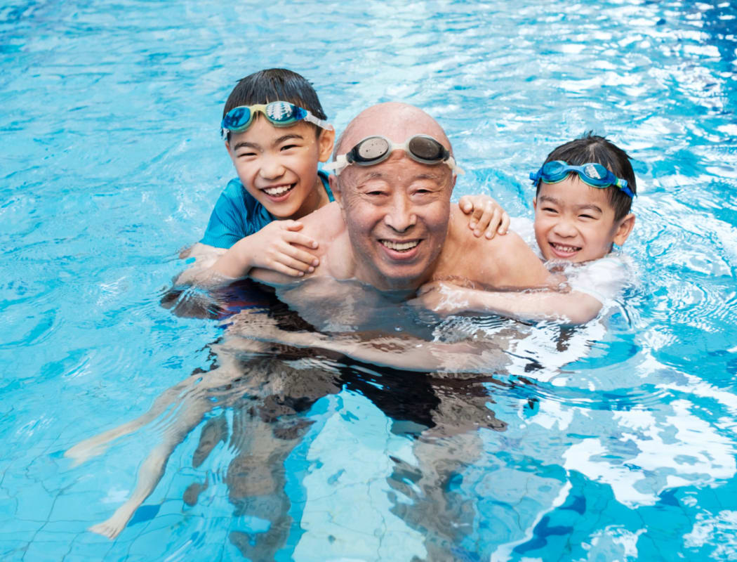 Senior and his grandchild hanging around in the swimming pool at  Avenida Palm Desert senior living apartments in Palm Desert, California