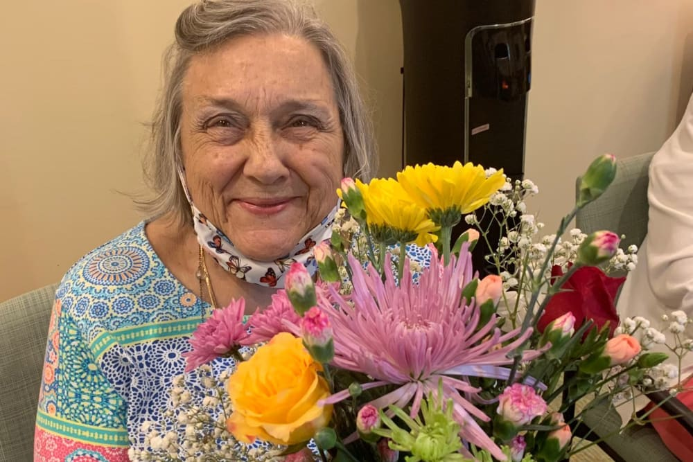 Woman resident smiling and holding flowers at Azpira at Windermere