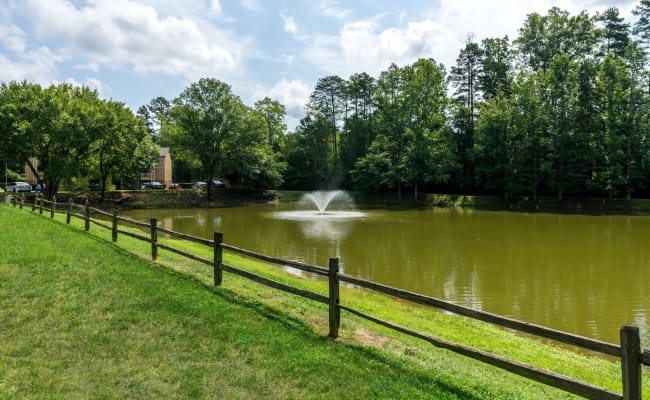 Large pond with a water fountain at Waters Edge Apartment Homes in Concord, North Carolina
