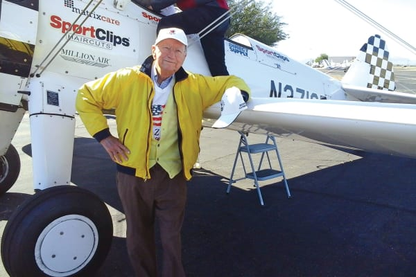 A resident from Colonial Gardens Gracious Retirement Living in Beverly, Massachusetts standing next to a plane