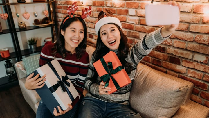 Two women smiling and holding wrapped gifts while taking a selfie.