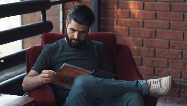A bearded man sitting in a chair reading a graphic novel or magazine.