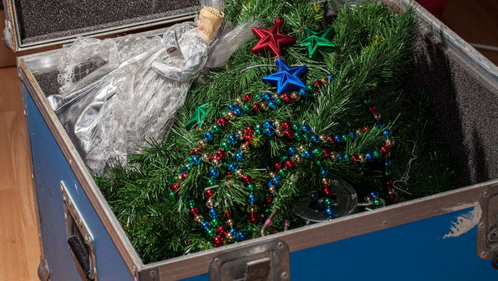An open storage container holds a disassembled holiday tree, decorative garland, and an angel tree-topper.