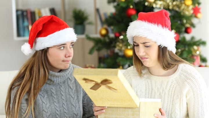 Two women with Santa hats sitting on a couch. One woman is holding an open gift box and making a distressed face.