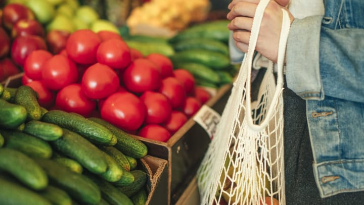 Person with a bag in their hand shopping and looking at fruits and vegetables.