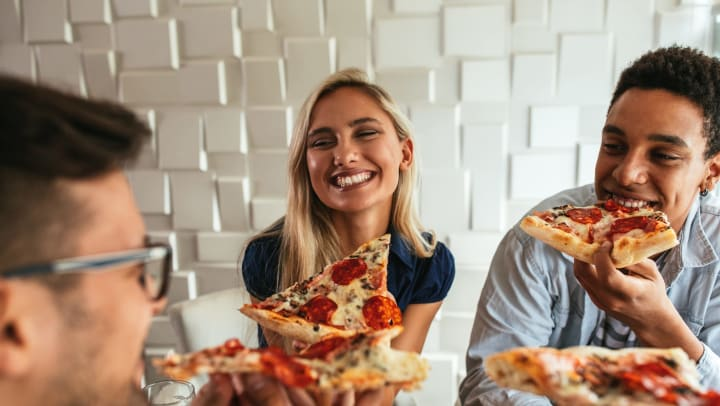 A group of smiling friends holding and eating slices of pepperoni pizza.