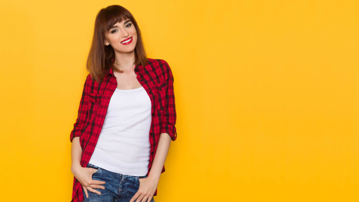 Woman wearing a red flannel button down with a white shirt underneath while posing in front of a yellow wall.