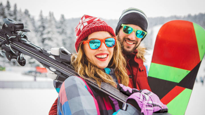 Woman holding skis and man holding snowboard with snowy mountains in the background