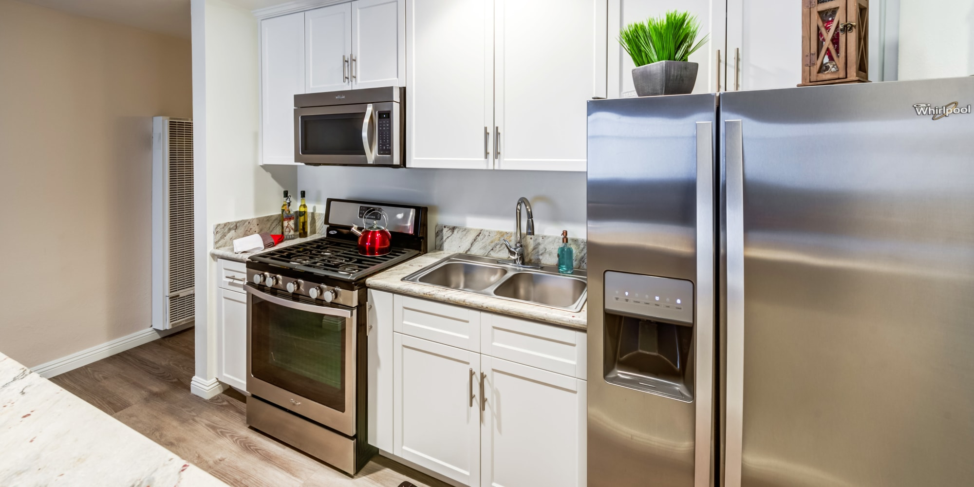 Hardwood flooring and stainless-steel appliances in a studio apartment's kitchen at Mediterranean Village in West Hollywood, California