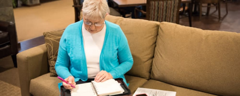 Resident making notes in the comfortable lounge at The Springs at Tanasbourne in Hillsboro, Oregon