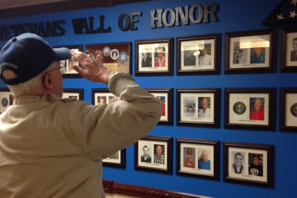 A veteran saluting a veterans wall of honor at Chesterfield Heights in Midlothian, Virginia