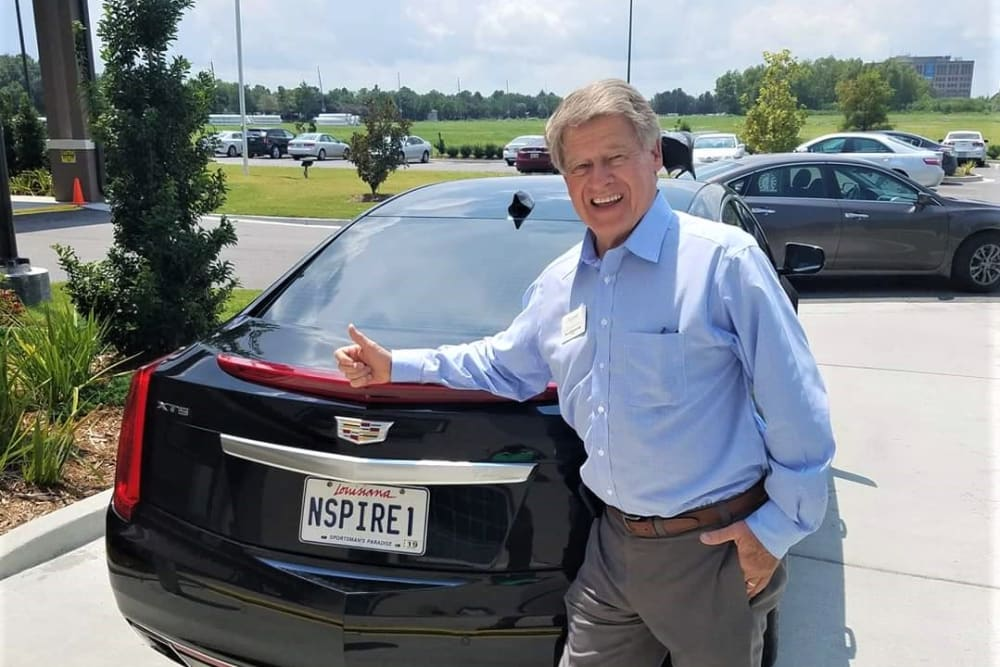 A resident posing with a car at Inspired Living Kenner in Kenner, Louisiana.