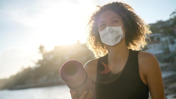 Woman holding yoga mat outside wearing a mask