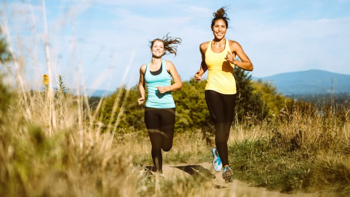 Two women, smiling and trail running in the sunshine over the top of a hill.