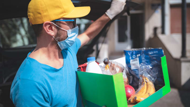 Man handing out a box of groceries to those in need in Keller, Texas near Olympus Waterford