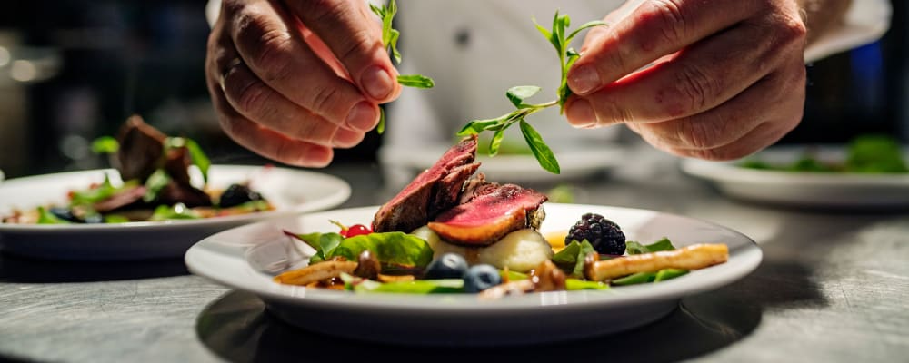 Chef putting the garnish on a complete dish at The Springs at Tanasbourne in Hillsboro, Oregon