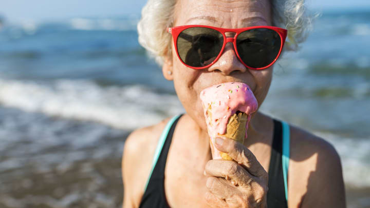 senior woman eating ice cream at the beach