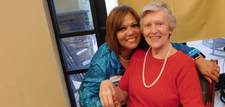 senior woman and staff member smiling