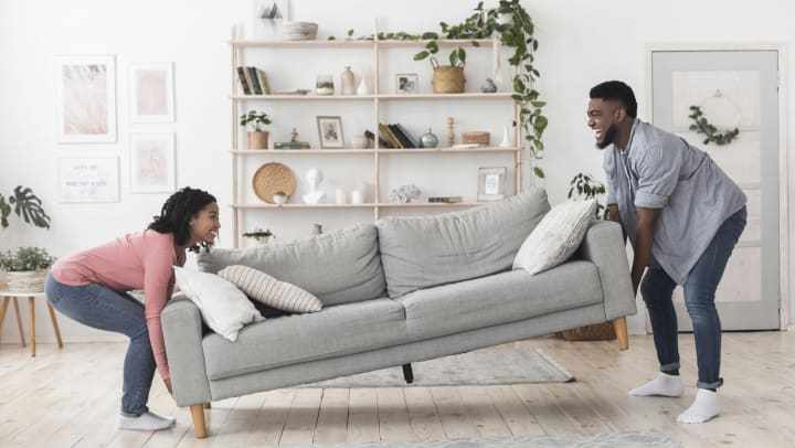 A smiling couple moving a sofa in their living room.