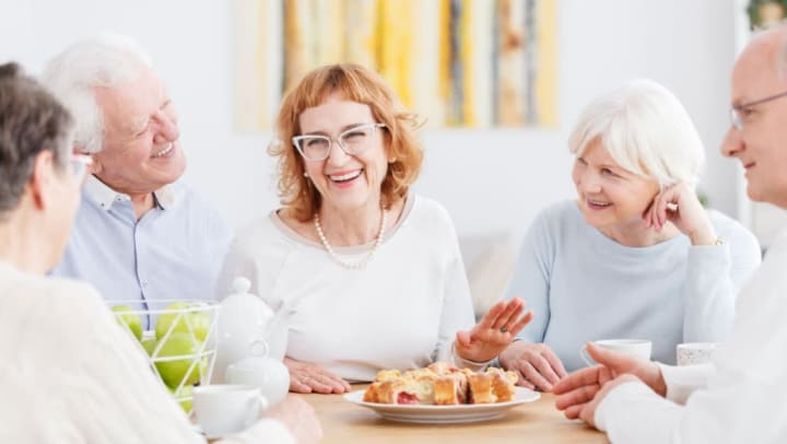 A group of residents socializing over tea and pastries at {{location_name}} in {{location_city}}, {{location_state_name}}